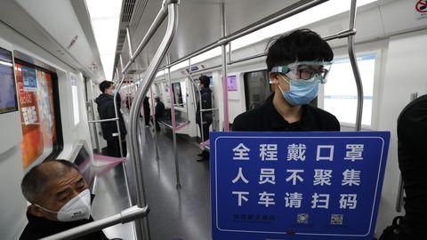 28.märts 2020, Wuhan. Hiinas on liikumispiirang läbi saanud. Ohutustööline palub reisijatel skaneerida QR-kood oma nime tuvastamiseks, lasta end kraadida ja kanda maske.