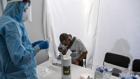 Kaitserõivastes tervishoiutöötaja võtab süljeproovi koroonaviiruse uuringu tarbeks Ram Manohar Lohia haiglas New Delhis, Indias, 31. juulil 2020.